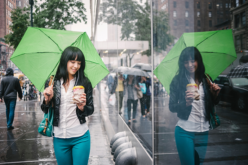 Woman walking with umbrella in the city